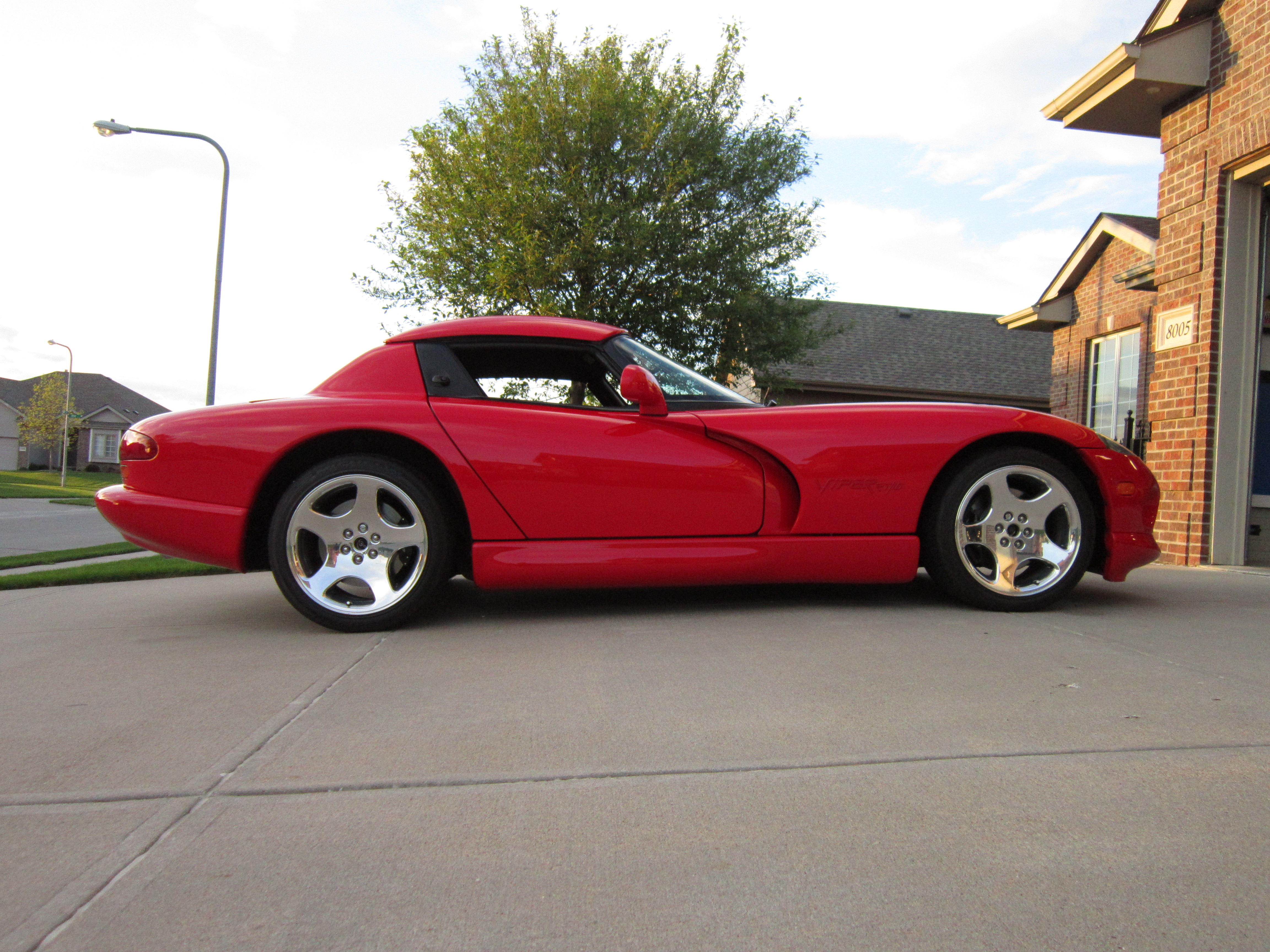 Covered in viper red paint with a black interior and chrome 5 spoked 18 inch wheels on michelin rubber this car has both the the convertible and hard top